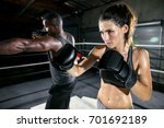 Small photo of Athletic female fighter throws a jab during training session with her male trainer