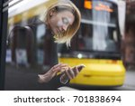 Small photo of Smiling blonde hipster girl waiting for public transport on bus stop chatting in social networks via smartphone,casually dressed female tourist using application for searching traffic schedule
