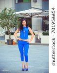 Small photo of Beautiful and stylish brunette woman american or European appearance in blue costume and silver accessorize walk in business part of city at sunny day