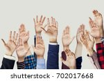 many hands raised together | Shutterstock . vector #702017668