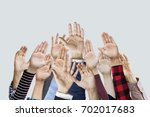 many hands raised together | Shutterstock . vector #702017683