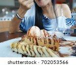 the girl hand is eating... | Shutterstock . vector #702053566