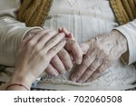closeup wrinkled hand holding a ... | Shutterstock . vector #702060508