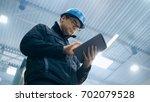 factory worker in a hard hat is ... | Shutterstock . vector #702079528
