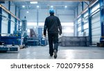 factory worker in a hard hat is ... | Shutterstock . vector #702079558