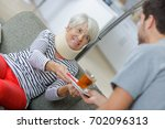 man passing cup of tea to lady... | Shutterstock . vector #702096313