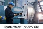 Factory worker is programming a CNC milling machine with a tablet computer. - stock photo