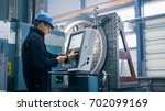 factory worker is programming a ... | Shutterstock . vector #702099169