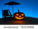 glowing carved pumpkin on sandy ... | Shutterstock . vector #702149800