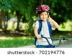 little boy learns to ride a... | Shutterstock . vector #702194776
