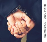 Small photo of close-up businessman hands in handcuffs. Businessman bribetaker or briber. Concept of fraud, detention, crime and bribery, toned image