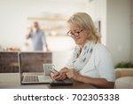 senior woman using mobile phone ... | Shutterstock . vector #702305338