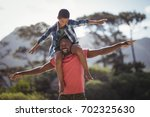 happy father carrying son on... | Shutterstock . vector #702325630