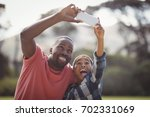father and son taking selfie... | Shutterstock . vector #702331069