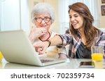 granddaughter showing her... | Shutterstock . vector #702359734