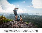 two hikers relax on top of a... | Shutterstock . vector #702367078