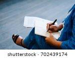 a woman writes a pen on a blank ...   Shutterstock . vector #702439174