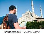a traveler in a baseball cap... | Shutterstock . vector #702439390