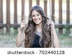 beautiful teenage girl in park... | Shutterstock . vector #702440128
