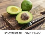 fresh avocado on cutting board... | Shutterstock . vector #702444100