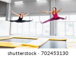 two young woman friends jumping ... | Shutterstock . vector #702453130