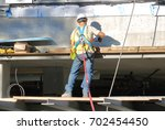 a construction worker uses a... | Shutterstock . vector #702454450
