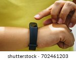 girl checks pulse on fitness... | Shutterstock . vector #702461203