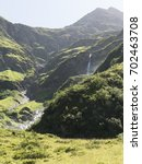 Small photo of Mountain waterfall in Alps. Scenic Alpine rocky alpine mountines of Sportgastein in summer. Picturesque mountain cascade, great mountain massif, sunny weather. Sport hiking landscape background.
