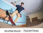 skateboarder performing a blunt ... | Shutterstock . vector #702497044