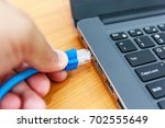 human hand plugging in a lan... | Shutterstock . vector #702555649