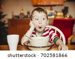 boy makes faces at the table.... | Shutterstock . vector #702581866