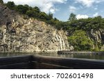 quarry with lake and pathway | Shutterstock . vector #702601498