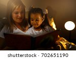 mother and child girl reading a ... | Shutterstock . vector #702651190