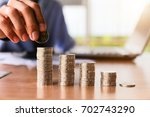 close up hand putting money... | Shutterstock . vector #702743290