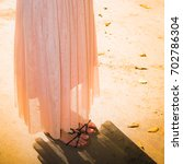 Small photo of Warm yellow orange colors and sunlit mood of autumn fallen leaves background with womens legs in fashionable pale mauve pink skirt and leather sandal shoes during Indian summer.