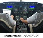 pilots in the cockpit of a... | Shutterstock . vector #702914014