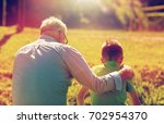Small photo of family, generation, relations and people concept - grandfather and grandson hugging outdoors