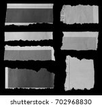 pieces of torn paper on black | Shutterstock . vector #702968830