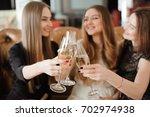 cheerful girls clinking glasses ... | Shutterstock . vector #702974938