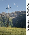 Small photo of Scenic Alpine rocky alpine valley of Sportgastein in summer with row of power lines and electricity pole. Picturesque mountain pasturelands, great mountain massif and sunny weather.