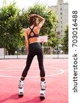 slim girl on the street posed... | Shutterstock . vector #703016488