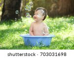 outdoor baby bathing. happy... | Shutterstock . vector #703031698
