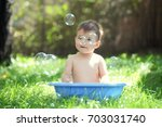 outdoor baby bathing. happy... | Shutterstock . vector #703031740