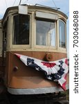 Small photo of Vintage trolley car with stats and stripes flag on front.