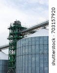 Small photo of Metal grain elevator in agricultural zone. Agricultural Silos. Building Exterior. Storage and drying of grains, wheat, corn, soy, sunflower on background of cloudy sky. Agriculture.