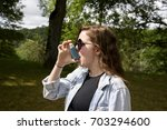 Teenage girl using inhaler (landscape). Long haired, teenage girl in denim jacket using a blue asthma inhaler. Taken in woodland on a sunny day. - stock photo