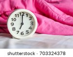 alarm clock on the bed with... | Shutterstock . vector #703324378