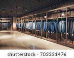 Interior of the business suit shop. Strict premium expensive suits hang in a row on hangers in large quantities - stock photo