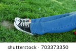 Small photo of A girl is resting in a clearing. Her legs are visible in sneakers and blue jeans. Rest of the tourist, active way of life, sports shoes, good weekend.