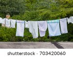 Stock photo fresh clean clothes are drying outside in the garden 703420060